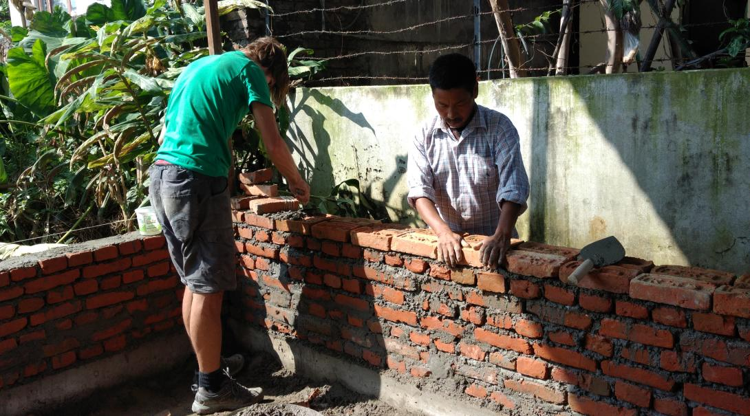 A volunteer is helping a local builder with building a wall during the Building Project in Nepal
